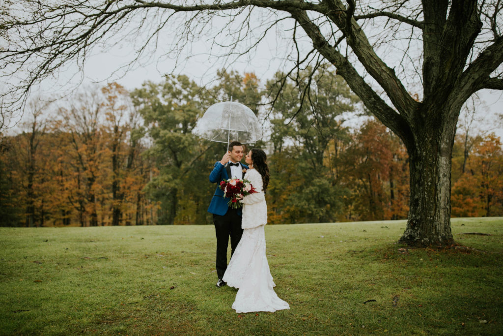 Wedding Couple posing with an umbrella in autumn