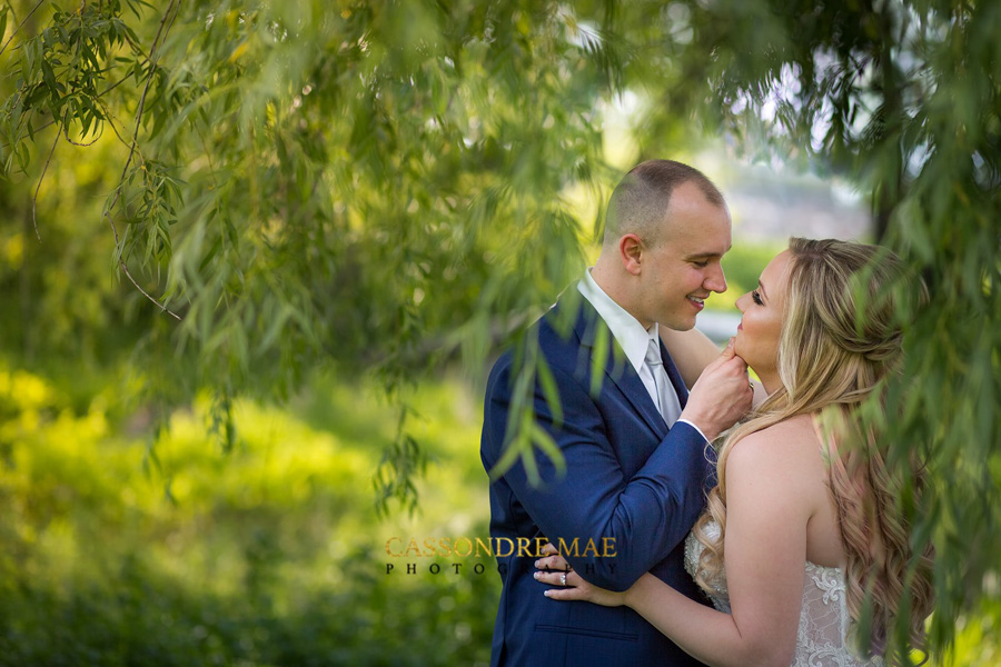 Couple shares a special moment under a willow tree at West Hills Country Club.