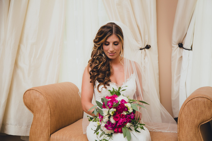 A bride poses in the wedding cottage with her bouquet.